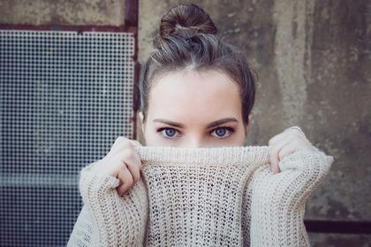 白いニットで顔を隠す女性