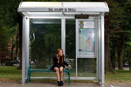 バス停に座る女性
