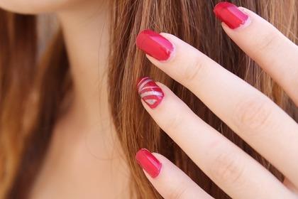 一つの指だけシルバーカラーの模様が可愛い赤ネイル