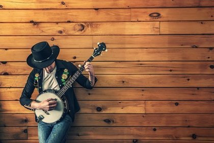 ジーパンを履いてギターを弾いている男性