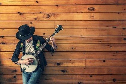 ギターを弾いているジーパンの男性