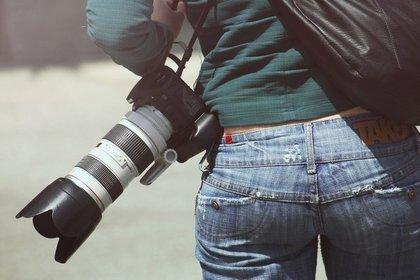 カメラを持ったジーパン姿の女性