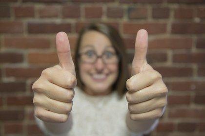 両手の親指を立てた女性