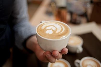 カフェラテのカップを持つ人