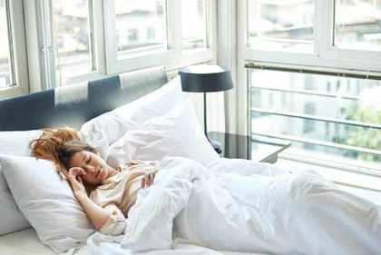 白いベッドで眠る女性