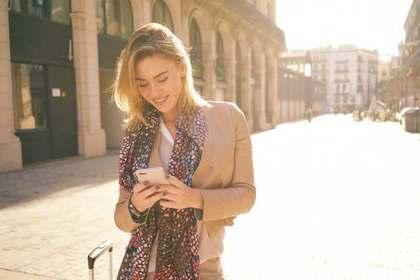 携帯見る女性・スーツケース