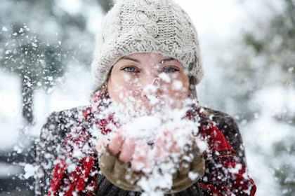 雪を吹きかける女性
