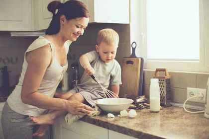 子どもと一緒に料理する女性