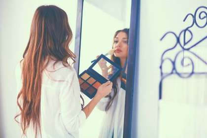 鏡の前でメイクをする女性