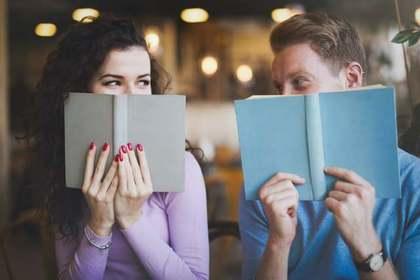 本で顔を隠すカップル