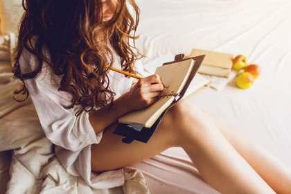 座って書く女性