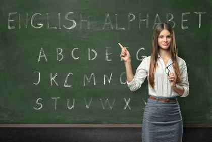 アルファベットが書かれた黒板と先生