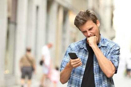 怒りながら携帯を見る男性