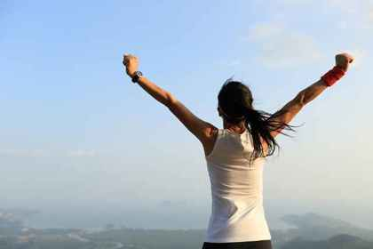 山頂で両手を広げる女性