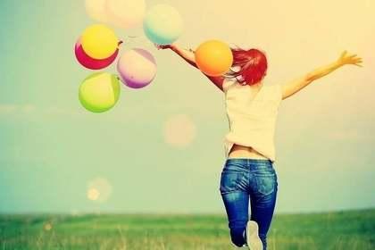 風船を持って野原を走る女性