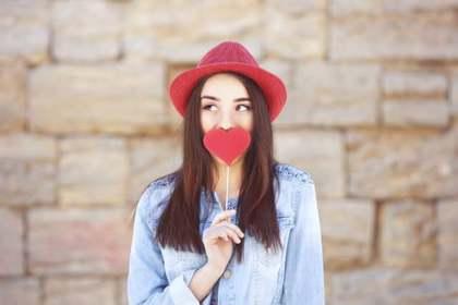 ハートで唇を隠す女性