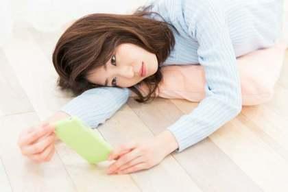 寝転んで携帯を見つめる女性