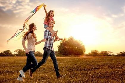 夕日の中の鮮やかな凧と3人の笑顔