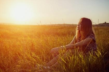 芝生の中に座る女性