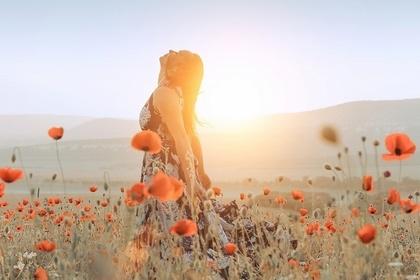 ポピーの花畑にたたずむ女性