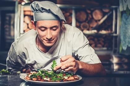 料理を盛りつけるシェフ