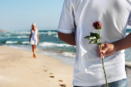 バラの花を隠し持つ男性