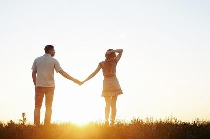 手をつないで夕日を見つめる男女