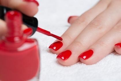 真っ赤なネイルカラーを塗っている手