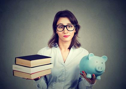 本と豚の貯金箱を両手に持つ女性