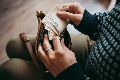 財布の中でお金を数えている人