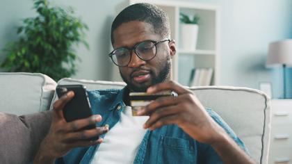 携帯とカードを手に持つ男性