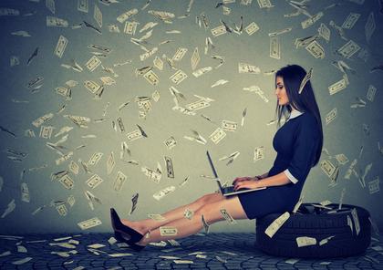 舞い上がるお金の中でパソコンを使う女性