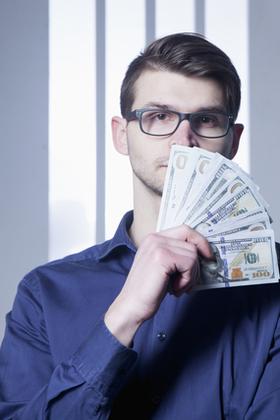 お金を扇形に持つ男性