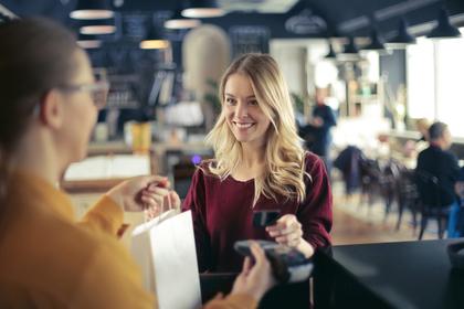カードで買い物する女性