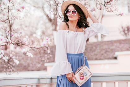 桜をバックに立つ女性