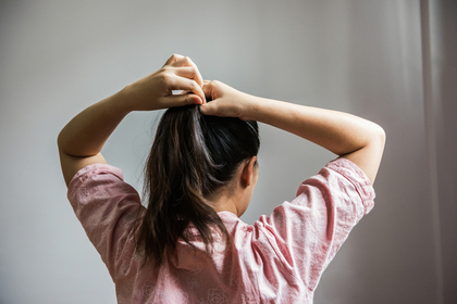 髪を縛る女性