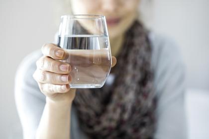 水が入ったグラスを持つ女性
