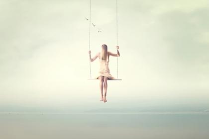 空中のブランコに乗る女性