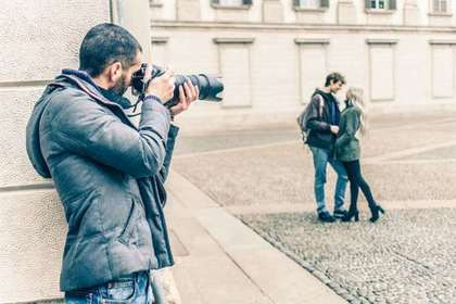 大きなカメラで撮影する男性