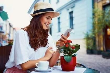友人の近況を見て笑う女性