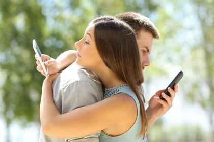 抱き合いながら携帯を見る二人