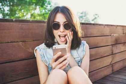 携帯を見て驚く女性