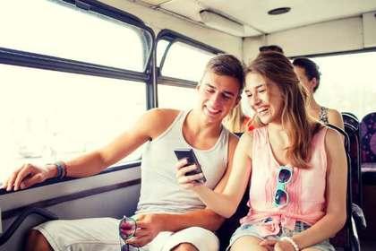 バスの中で携帯を見る男女