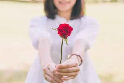 薔薇の花を差し出す女性