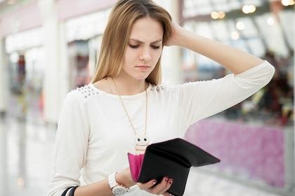 携帯を見て頭を触る女性