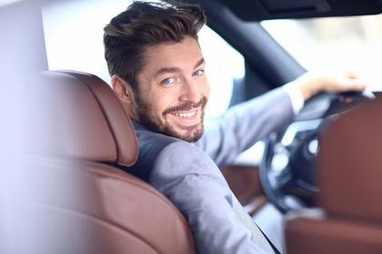 運転席から後ろを見る男性