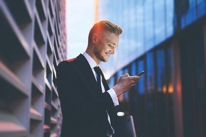 スーツ姿で携帯を見る男性
