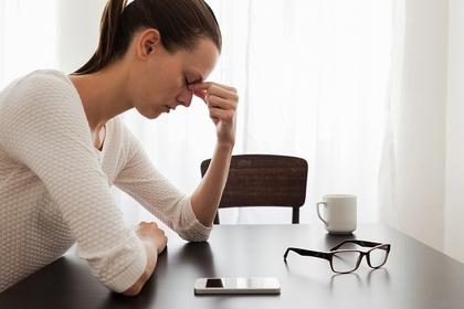 眉間を抑える女性