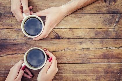 コーヒーカップを持つ人